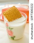 Small photo of square cookie soaked in a mug of milk close up