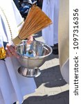Small photo of an altar boy holding a silver pot with sparkling water and a sprinkler