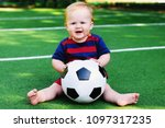 Small photo of Happy little blonde girl in striped navy and red shirt sitting with soccer ball at football field. Smilng child in sports uniform playing with a ball at training ground. Outdoor sport activity concept