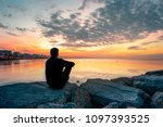 Man Sitting On A Rock Watching...