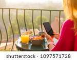 woman using phone at breakfast... | Shutterstock . vector #1097571728