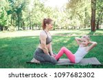 Two girls are excercising in park. Woman is sitting on her knees and holding her daughter