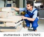 bulder man is choosing cement... | Shutterstock . vector #1097727692