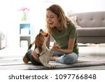 Stock photo young woman playing with her dog at home 1097766848