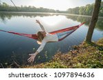 young woman by the lake hanging ... | Shutterstock . vector #1097894636