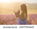a little girl with a basket in... | Shutterstock . vector #1097954645