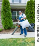 man vacuuming the pathway in... | Shutterstock . vector #1098106022