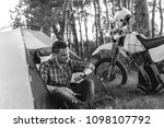 Small photo of man is sitting in a tourist tent and looks at the wath. Camping in forest, motorcycle touring, dual sport enduro, tent and off road adventure motorcycle, active life style concept, black and white bw