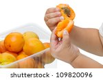 Hands of a child with apricot isolated on white background - stock photo