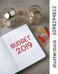 "Small photo of Notebook with text ""BUDGET 2019"", money jar and coins background. Budget planning concept."