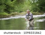 fisherman fly fishing in river | Shutterstock . vector #1098331862