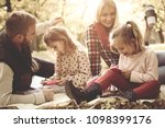 Small photo of Little sisters coloring book. Family sitting on falling leaven park.