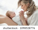 young mother holding her... | Shutterstock . vector #1098528776