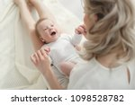 young mother holding her... | Shutterstock . vector #1098528782