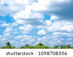 Small photo of Sky blue or azure sky and clouds on forest background. Everything lies above surface atmosphere outer space is sky. Cloud is aerosol comprising visible mass of liquid droplets frozen in air.