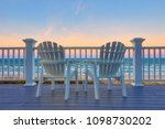 Empty Adirondack chair on a deck balcony overlooking the beach and the ocean at sunset