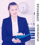 Small photo of Young manager woman in black suit is signing agreement papers of financial nature at office.