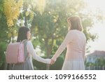asian mother holding hand of... | Shutterstock . vector #1099166552
