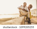 beautiful black race african couple in love and vacation sit down enjoying together with big smiles and laugh. casual clothes like fashion style with nice sunset backlight on the background. tenerife.