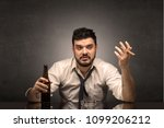 Small photo of Young drunk man at his office with free dark copyspace