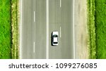 Stock photo aerial photo a white car is driving along the highway parallel to the road markings concept of 1099276085
