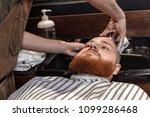 barber washing hair of bearded... | Shutterstock . vector #1099286468