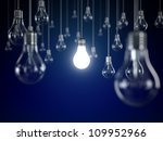 Hanging light bulbs with glowing one isolated on dark blue background - stock photo