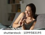 happy woman eating chocolate in ... | Shutterstock . vector #1099583195