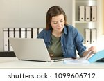 casual intern working comparing ... | Shutterstock . vector #1099606712