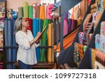 mature fabric store owner... | Shutterstock . vector #1099727318