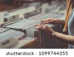 young woman browsing records in ... | Shutterstock . vector #1099744355