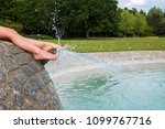 feet of a young child splashing ... | Shutterstock . vector #1099767716