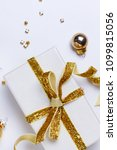 Small photo of Christmas flat lay frame with git box with golden bow