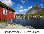 Typical red rorbu hut with sod roof in a picturesque town of Reine on Lofoten islands in Norway - stock photo
