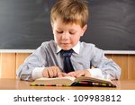 Cute elementary aged boy sitting at the desk with books - stock photo