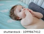 little baby lying down in a bed ... | Shutterstock . vector #1099867412