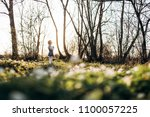 the small girl stands near trees   Shutterstock . vector #1100057225
