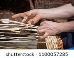 hands of a basket maker are... | Shutterstock . vector #1100057285