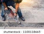 male worker repairing driveway... | Shutterstock . vector #1100118665