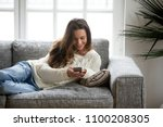 happy young woman lying on sofa ... | Shutterstock . vector #1100208305