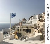 Small photo of Santorini View With Greece Flag