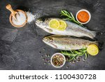fresh trout on dark table with... | Shutterstock . vector #1100430728