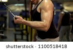 muscular man looking at his... | Shutterstock . vector #1100518418