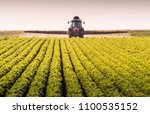 tractor spraying pesticides on... | Shutterstock . vector #1100535152