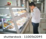 Stock photo blurred image of man wearing business suit in canteen or office cafeteria at food display cabinet 1100562095