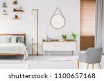 Stock photo scandinavian style white room interior with round mirror on the wall wooden bed with pillows and 1100657168