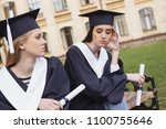 Small photo of Two amicable students feeling very sentimental on their graduation day while sitting near university
