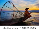 Small photo of INTHA, MYANMAR - FEBRUARY 18, 2018: The portrait of Burmese fisherman, sitting in his kayak with a addle and large conical net on sunset on Inle Lake, on February 18 in Intha.