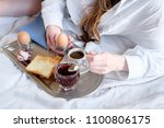 Small photo of Breakfast in bed in hotel. Redhead gird after taking shower has a breakfast in bed in hotel room.