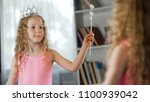 little girl looking at mirror... | Shutterstock . vector #1100939042